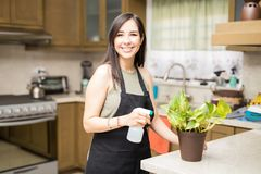Pretty woman caring for potted flowers at home. Happy young woman watering plant using sprinkling can and smiling Royalty Free Stock Image