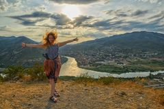Happy young woman near Jvari Monastery of Georgia. Happy young woman waving hair and hands near windy Jvari Monastery of Georgia, overlooking Mtsheta town and Royalty Free Stock Photo