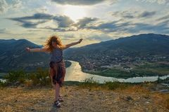 Happy young woman near Jvari Monastery of Georgia. Happy young woman waving hair and hands near windy Jvari Monastery of Georgia, overlooking Mtsheta town and Royalty Free Stock Images