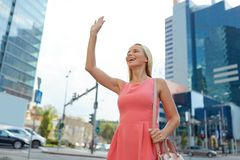 Happy young woman waving hand on city street Stock Images