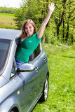 Happy young woman waving out the window Stock Photos