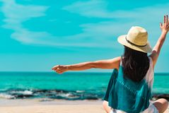 Happy young woman wear straw hat sit and raised hand at sand beach. Relaxing and enjoy holiday at tropical paradise beach royalty free stock photo