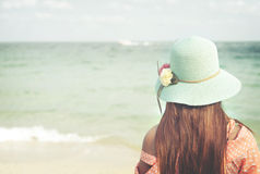 Happy young woman wear straw hat - stand on the beach in summer. Rear of happy young woman wear straw hat - stand on the beach in summer. Vintage color tone Stock Photo