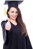 Happy young woman wearing cap and gown with thumb up Stock Photos