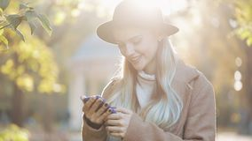 Happy young woman wearing a coat using smartphone standing in autumn park. Technology outdoors. Sunlight stock footage