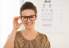 Happy young woman wearing eyeglasses in front of Snellen chart Royalty Free Stock Photos