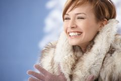 Happy young woman wearing fur coat. Portrait of happy young woman wearing fur coat, enjoying winter sunshine Stock Images