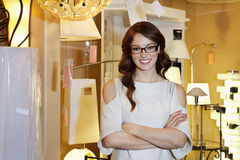 Happy young woman wearing glasses standing with arms crossed in store Stock Photography