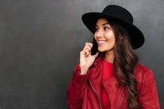 Happy young woman wearing hat talking by mobile phone. Image of happy young woman wearing hat standing over dark grey wall chalkboard talking by mobile phone Royalty Free Stock Photography
