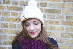 Happy young woman wearing knit hat and scarf looking down Stock Photo