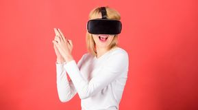 Happy young woman wearing virtual reality goggles watching movies or playing video games. Happy woman exploring. Augmented world, interacting with digital stock photography
