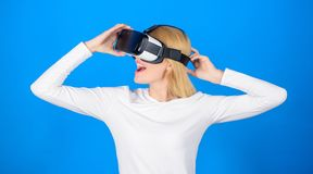 Happy young woman wearing virtual reality goggles watching movies or playing video games. Person with virtual reality. Helmet isolated on blue background. Woman royalty free stock photos