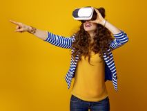 Happy young woman wearing VR headset and pointing at something Royalty Free Stock Images