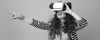 Happy young woman wearing VR headset and pointing at something Royalty Free Stock Image