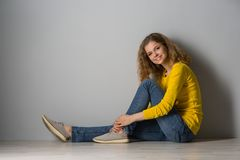 Happy young woman wearing yellow shirt and jeans shorts  over gr. Image of happy young woman wearing yellow shirt and jeans shorts  over grey background Stock Photo