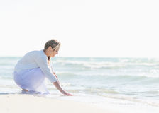 Happy young woman wetting hands in sea Stock Photos