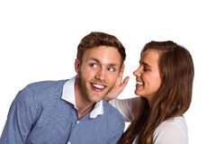 Happy young woman whispering secret into friends ear Royalty Free Stock Photography