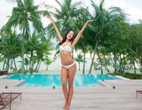 Happy young woman in white bikini swimsuit dancing Stock Image