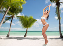 Happy young woman in white bikini swimsuit dancing Royalty Free Stock Photography