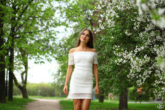 Happy young woman in white dress against the background spring Royalty Free Stock Image
