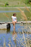 Happy young woman in white dress sitting on pier by river or lake Stock Photo
