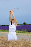 Happy young woman in white dress standing in cornfield. Cheerful lady standing in cornfield, stretches her arms upwards, holding some ears of wheat. In the Royalty Free Stock Photography