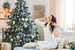 Happy young woman in white knitted sweater stretching royalty free stock images