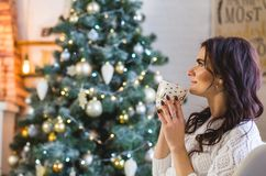 Happy young woman in white knitted wearing with cup of coffee or tea at home royalty free stock photo
