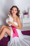 Happy young woman with a white rabbit in the studio Royalty Free Stock Photography