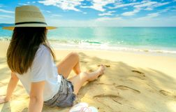 Happy young woman in white shirts and shorts sitting at sand beach. Relaxing and enjoying holiday at tropical paradise beach with. Blue sky and clouds. Girl in royalty free stock photos