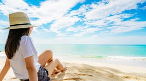 Happy young woman in white shirts and shorts sitting at sand beach. Relaxing and enjoying holiday at tropical paradise beach. With blue sky and clouds. Girl in stock photo