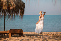 Happy young woman in a white sundress walking along the seashore Royalty Free Stock Photography
