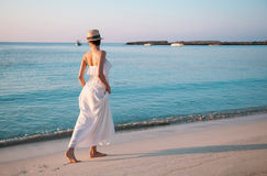 Happy young woman in a white sundress walking along the seashore Royalty Free Stock Photo