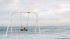 Happy young woman in white swimsuit riding on swing enjoying sea view. Vacation concept stock video footage