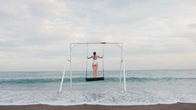 Happy young woman in white swimsuit riding on swing enjoying sea view. Vacation concept stock footage