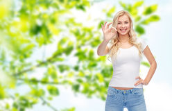 Happy young woman in white t-shirt showing ok sign Stock Photos