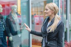 Happy young woman window shopping Stock Photos