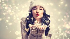 Happy young woman blowing snow and hearts. Happy young woman with winter clothes blowing snow and hearts Royalty Free Stock Photos