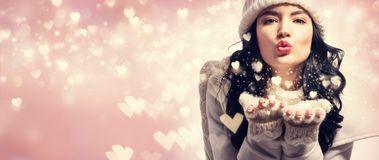 Happy young woman blowing snow and hearts. Happy young woman with winter clothes blowing snow and hearts Royalty Free Stock Photo