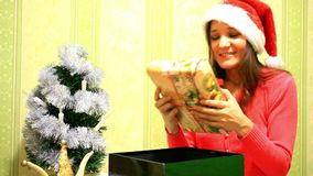 Happy young woman in winter hat open box gift near. Christmas tree. 1920x1080 stock video