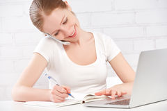 Happy Young Woman Working At A Laptop At Home Royalty Free Stock Photo