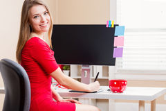 Happy young woman working in her home office royalty free stock photography