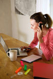Happy young woman working from home Royalty Free Stock Image