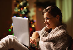 Happy young woman working on laptop in front of christmas tree Stock Photos