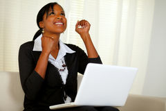 Happy young woman working on laptop and looking up. Portrait of a happy young entrepreneur woman celebrating a business victory on laptop and looking up while Stock Photography