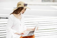 Happy young woman working with a laptop sitting on a bench. Stock Images