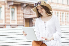 Happy young woman working with a laptop sitting on a bench. She smiles. Student is white with brown hair. The woman dressed in brown jeans, a white tunic. On Stock Images