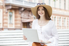 Happy young woman working with a laptop sitting on a bench. Royalty Free Stock Photography