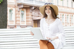 Happy young woman working with a laptop sitting on a bench. Stock Photos