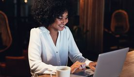 Happy young woman working late in office stock images